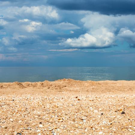 foreground focus: Foreground focus - sand and shelly beach close up and dark blue clouds over sea. Coastline of Sea of Azov, Temryuk bay, Golubitskaya resort, Taman peninsula, Kuban, Russia Stock Photo