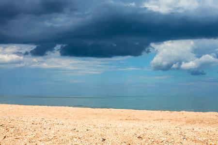 foreground focus: Foreground focus - landscape with sand beach and dark blue rain clouds over sea. Coastline of Sea of Azov, Temryuk bay, Golubitskaya resort, Taman peninsula, Kuban, Russia
