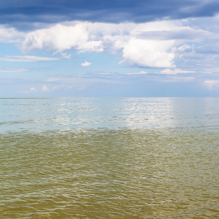 krasnodar region: natural square background - Azov Sea seascape with calm green water and blue sky with white and rain clouds. Temryuk bay, Golubitskaya resort, Taman peninsula, Kuban, Russia Stock Photo