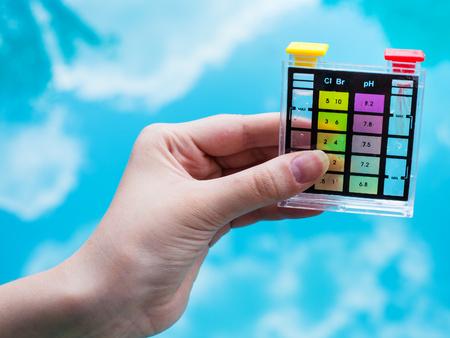 Controleer het pH-niveau in het blauwe buitenzwembad door middel van chemische tester