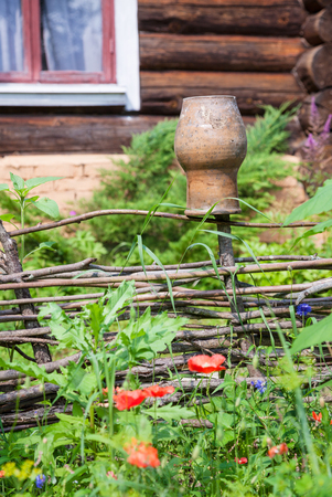 rural scenery - wattle fence with clay pot and old country cottage
