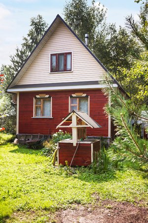 draw-well in front of little country cottage in summer day Stock Photo