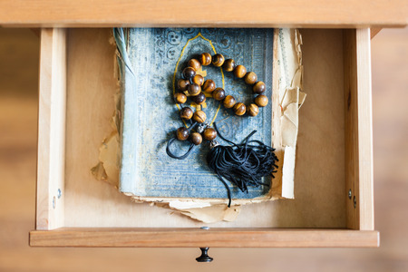 bedtable: above view of rosary on shabby religious book in open drawer of nightstand