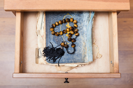 bedtable: top view of rosary on old religious book in open drawer of nightstand