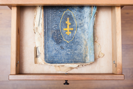 bedtable: top view of ancient ritual book in open drawer of nightstand