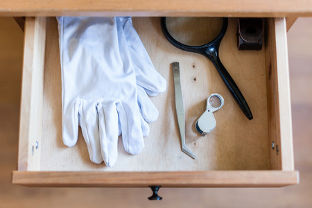 bedtable: above view of magnifier, forceps and white gloves in open drawer of nightstand Stock Photo