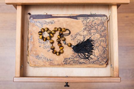 bedtable: top view of rosary on ansient book in open drawer of nightstand