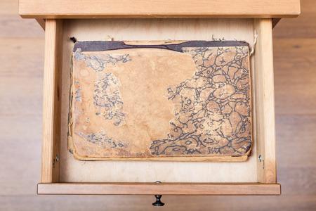 nightstand: top view of ancient book in open drawer of nightstand