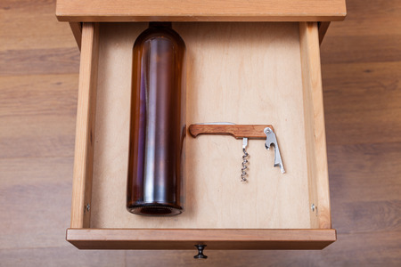 bedtable: top view of empty wine bottle and corkscrew in open drawer of nightstand