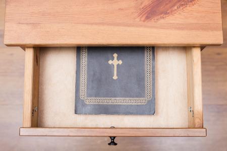 nightstand: top view of Bible book in open drawer of nightstand
