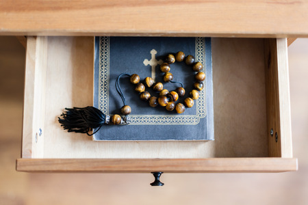 top view of rosary on Bible book in open drawer of nightstand Stock Photo
