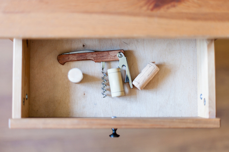 bedtable: above view of foldable corkscrew and few corks in open drawer of nightstand Stock Photo