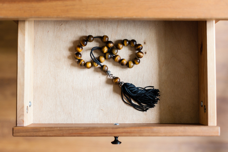 bedtable: above view of rosary from tiger-eye gems in open drawer of nightstand