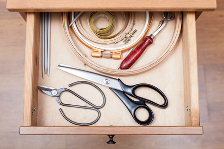 bedtable: top view of accessories for embroidery in open drawer of nightstand