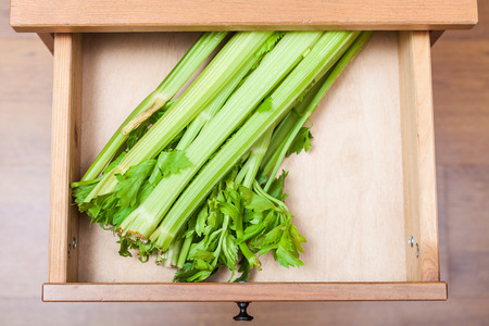 nightstand: top view of celery stalks in open drawer of nightstand