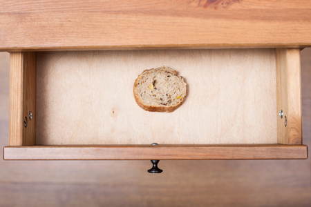 bedtable: top view of slice of bread in open drawer of nightstand