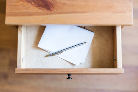 bedtable: above view of folded sheet of paper and pen in open drawer of nightstand