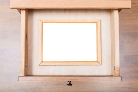 bedtable: top view of narrow picture frame with cut out canvas in open drawer of nightstand