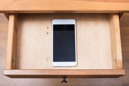 nightstand: above view of mobile phone in open drawer of nightstand Stock Photo