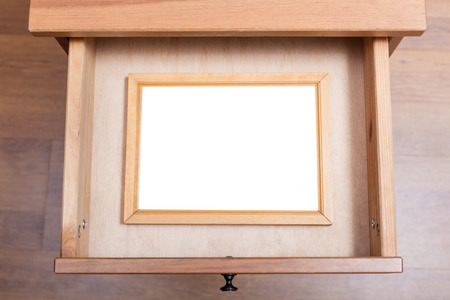 bedtable: above view of wooden picture frame with cut out canvas in open drawer of nightstand