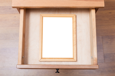 bedtable: top view of simple picture frame with cut out canvas in open drawer of nightstand