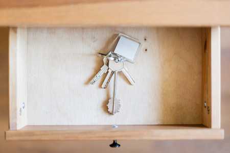 bedtable: above view of bunch of door keys with keyfob in open drawer of nightstand Stock Photo