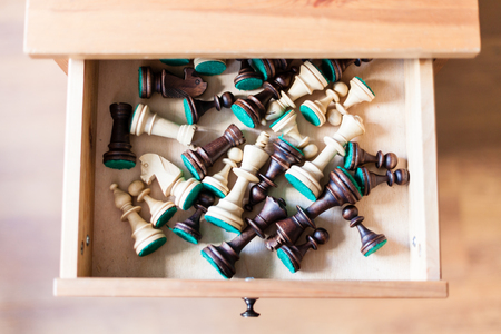 nightstand: top view of chess figures in open drawer of nightstand Stock Photo