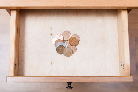 bedtable: above view of several of british coins in open drawer of nightstand