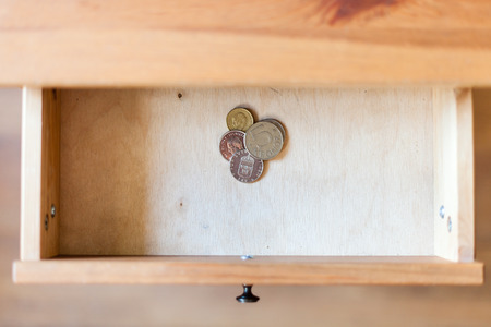 few: above view of few Swedish coins in open drawer of nightstand