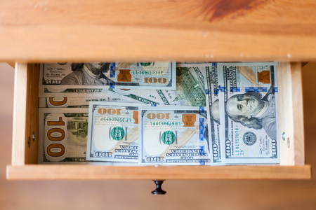 bedtable: top view of many one hundred dollar banknotes on bottom of open drawer of nightstand