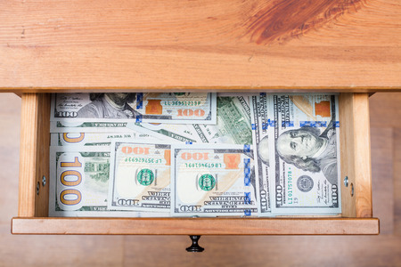 bedtable: above view of many one hundred dollar bills on bottom of open drawer of nightstand