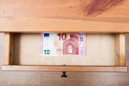 bedtable: top view of one ten euro banknote in open drawer of nightstand