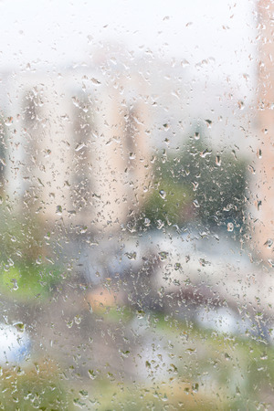 trickle down: rainy weather in city - view of wet window glass of apartment house