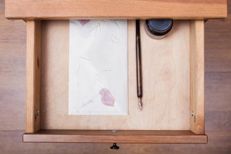 nib: above view of nib pen, ink, vintage envelope in open drawer of nightstand