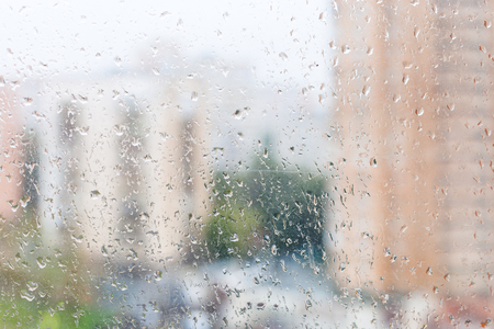 trickle down: rainy weather in city - view of wet window glass of urban house