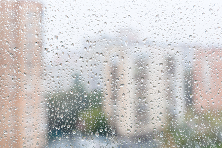 trickle down: rainy weather in city - view of raindrops on window glass of urban house