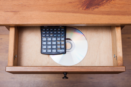 bedtable: above view of scientific calculator and disk with the experimental data in open drawer of nightstand Stock Photo