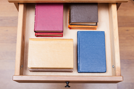 bedtable: above view of pack ofl little books in open drawer of nightstand Stock Photo