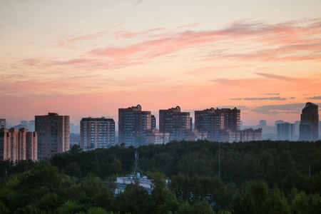 early summer: early sunrise in city in summer morning