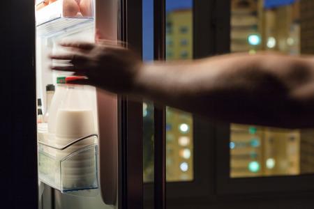 reaches: hand reaches for milk bottle in home fridge in night