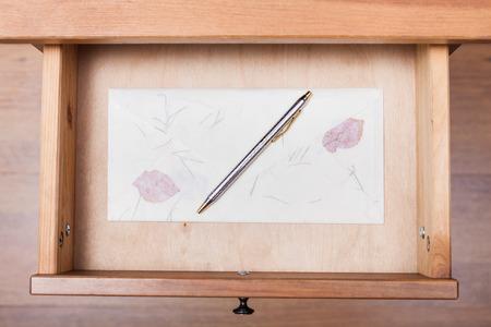 ballpen: above view of ballpen on vintage envelope in open drawer of nightstand