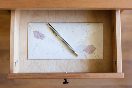 bedtable: top view of silver pen on vintage envelope in open drawer of nightstand