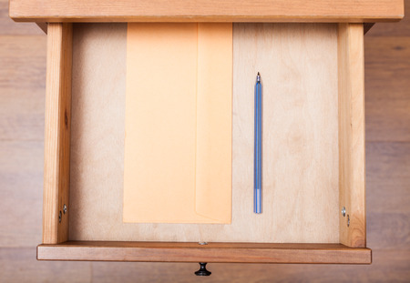 bedtable: top view of blue pen and envelope in open drawer of nightstand