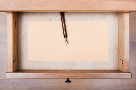 bedtable: top view of nib pen, paper envelope in open drawer of nightstand