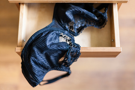 nightstand: top view of black brassiere in open drawer of nightstand
