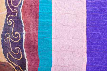 sewn up: textile background - stitched pieces of clenched silk fabrics and painted batik Stock Photo
