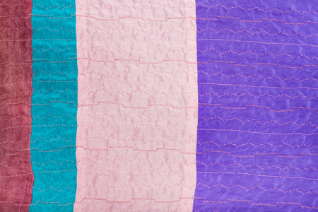 sewn up: textile background - sewn pieces of clenched silk fabrics