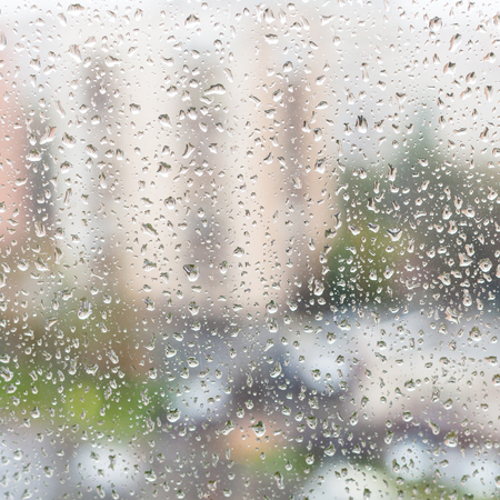 trickle down: rainy weather in city - view of rain drops on window glass of apartment house