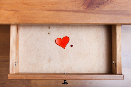 bedtable: top view of two red glass hearts in open drawer of nightstand Stock Photo