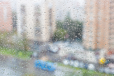 trickle down: rainy weather in city - view of raindrops on windowpane of urban house
